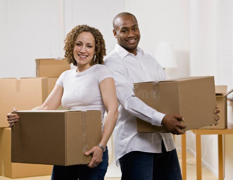 Glückliche Paare, die in neues Haus sich bewegen stockbilder