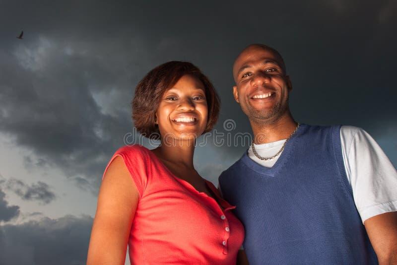 Glückliche Paare, die am Sonnenuntergang aufwerfen stockfoto