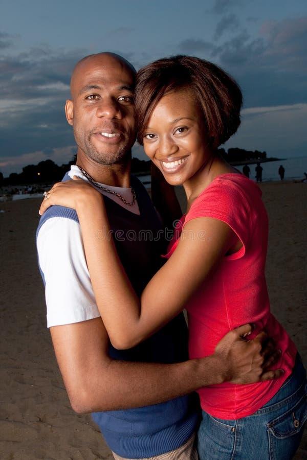 Glückliche Paare, die am Sonnenuntergang aufwerfen stockfotos
