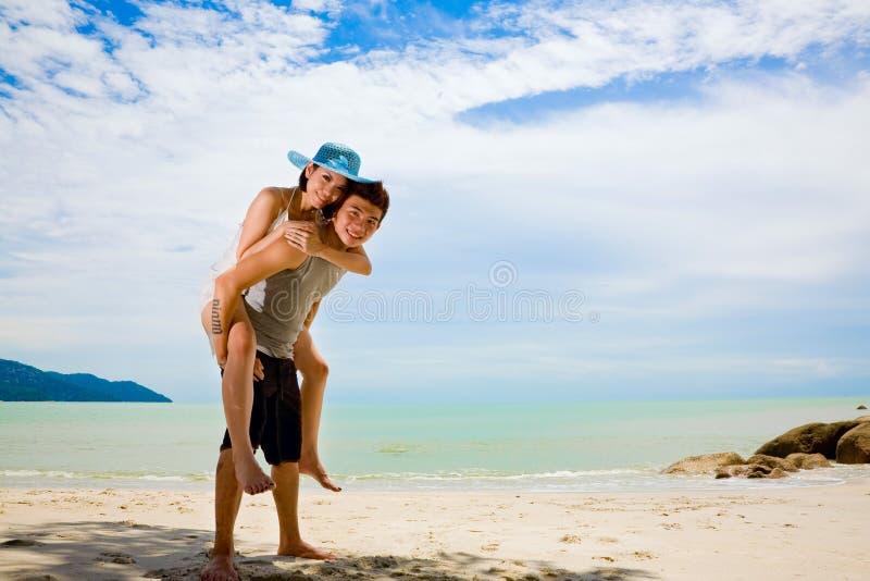 Glückliche Paare, die Spaß am Strand haben stockfoto