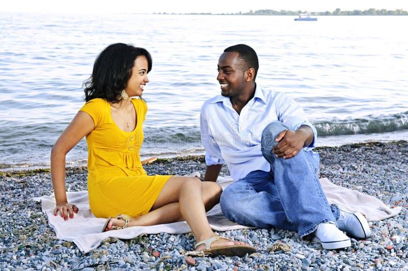Glückliche Paare, die am Strand sitzen lizenzfreie stockfotos