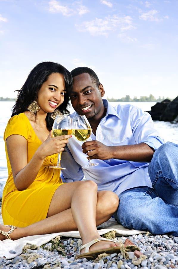 Glückliche Paare, die Wein auf Strand essen lizenzfreie stockbilder