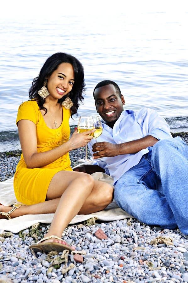 Glückliche Paare, die Wein auf Strand essen lizenzfreies stockbild