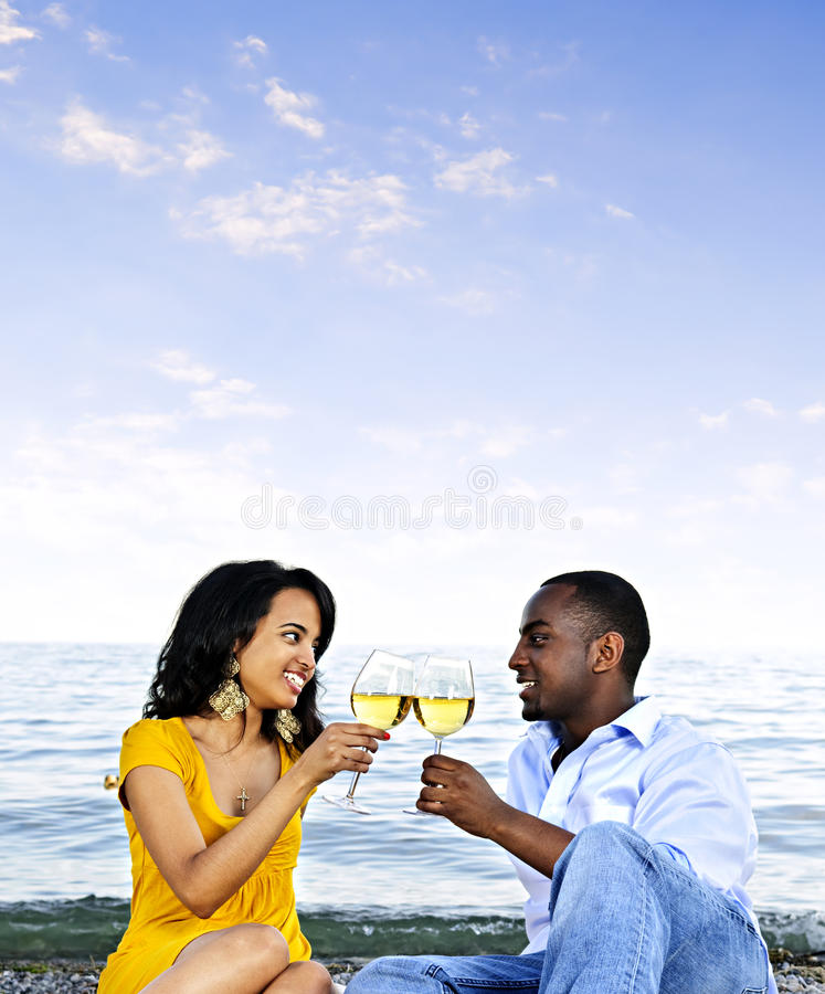 Glückliche Paare, die Wein auf Strand essen stockfotografie