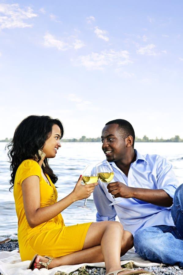 Glückliche Paare, die Wein auf Strand essen lizenzfreies stockfoto