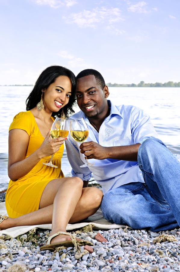 Glückliche Paare, die Wein auf Strand essen stockbilder