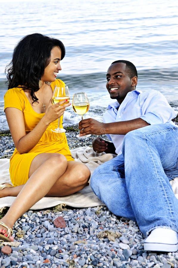 Glückliche Paare, die Wein auf Strand essen stockbild