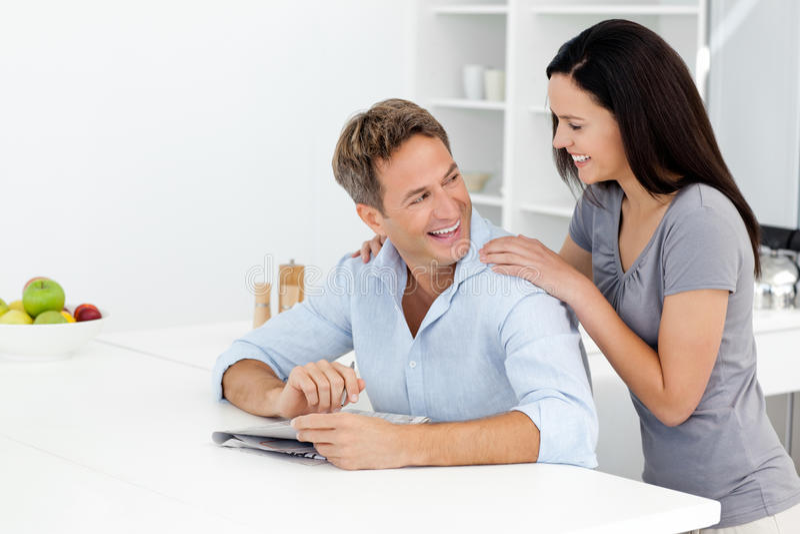 Glückliche Paare, die zusammen ein verschlüsseltes Kreuzworträtsel tun stockbilder