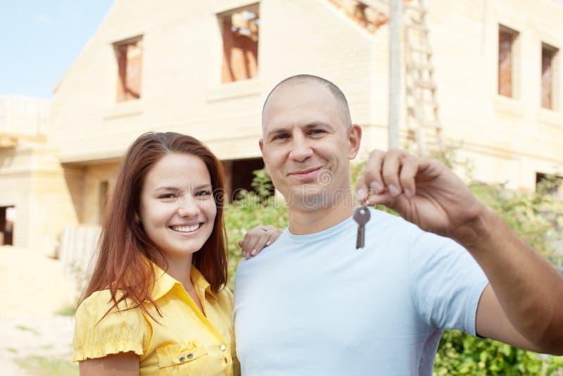 Glückliche Paare gegen neues Haus des Gebäudes lizenzfreies stockfoto