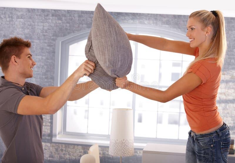Glückliche Paare im Kissenkampf lizenzfreie stockfotografie