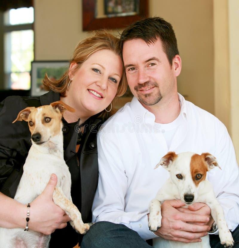 Glückliche Paare mit ihren Hunden lizenzfreie stockbilder