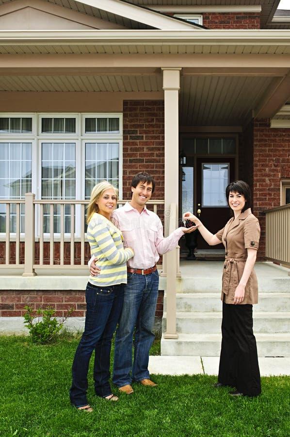 Glückliche Paare mit Immobilienmakler lizenzfreie stockbilder