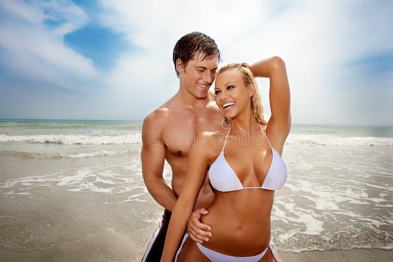 Glückliche Paare am Strand lizenzfreie stockfotos