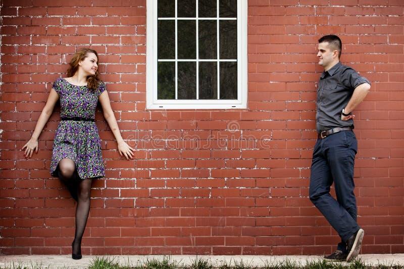 Glückliche Paare und Haus mit Backsteinmauer stockfoto