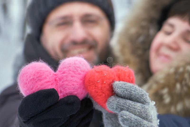 Glückliche Paare von mittlerem Alter, die draußen in den Händen zwei woolen Herzen halten lizenzfreies stockbild