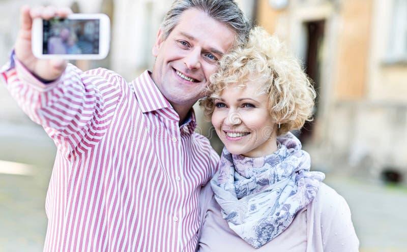 Glückliche Paare von mittlerem Alter, die draußen selfie durch intelligentes Telefon nehmen lizenzfreies stockbild