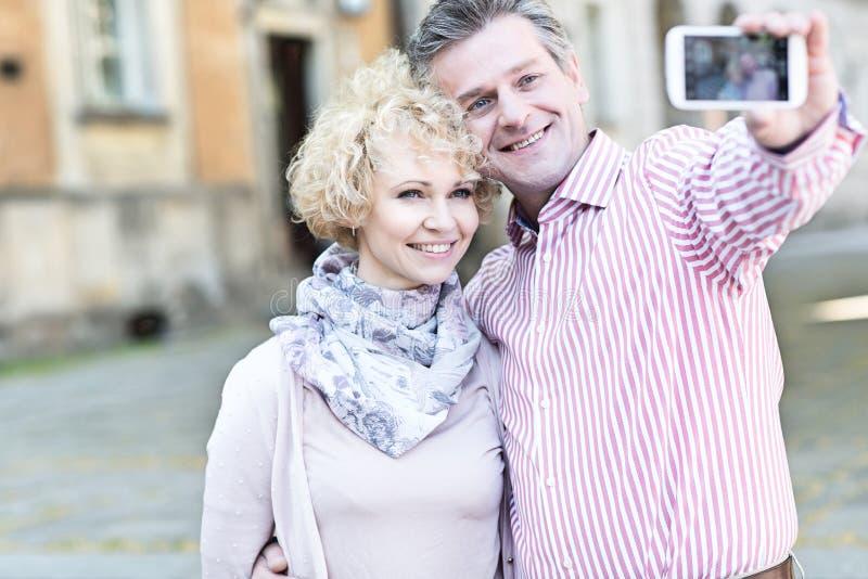 Glückliche Paare von mittlerem Alter, die selfie durch intelligentes Telefon in der Stadt nehmen stockfotos