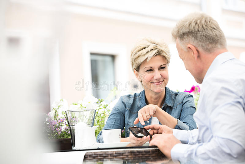 Glückliche Paare von mittlerem Alter unter Verwendung des Handys am Straßencafé stockfotografie