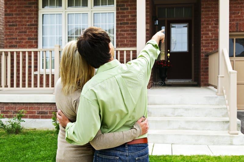 Glückliche Paare vor Haus stockfotografie