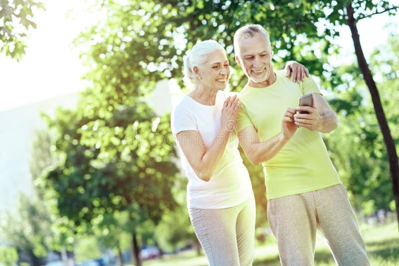 Glückliche Pensionäre, die den Smartphone betrachten stockfoto