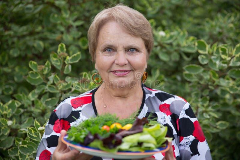 Glückliche Pensionärfrau mit Gemüse an der Datscha lizenzfreies stockfoto