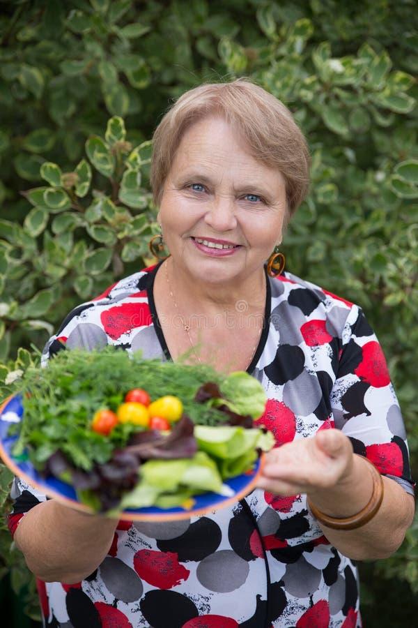 Glückliche Pensionärfrau mit Gemüse an der Datscha stockbild