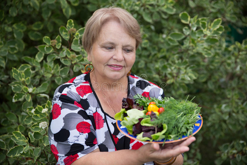Glückliche Pensionärfrau mit Gemüse an der Datscha lizenzfreies stockbild