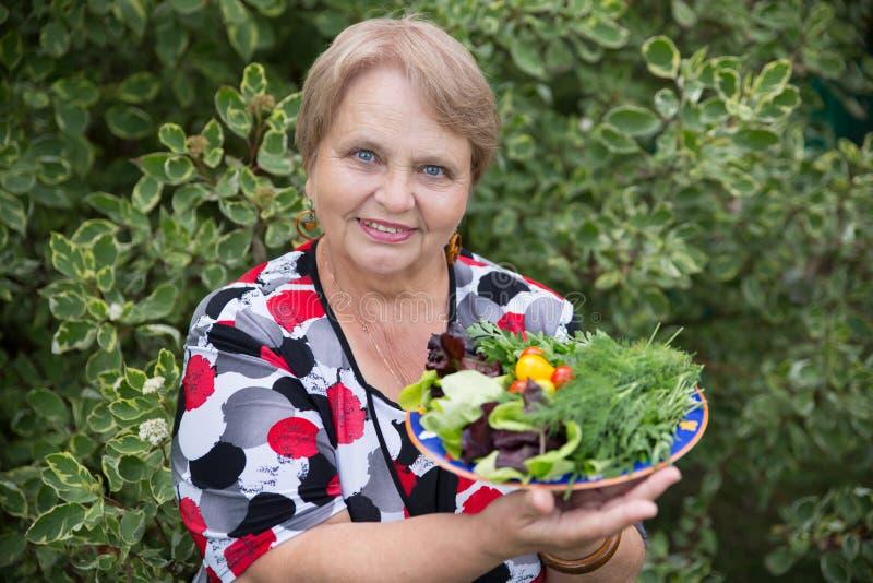 Glückliche Pensionärfrau mit Gemüse an der Datscha stockfotos