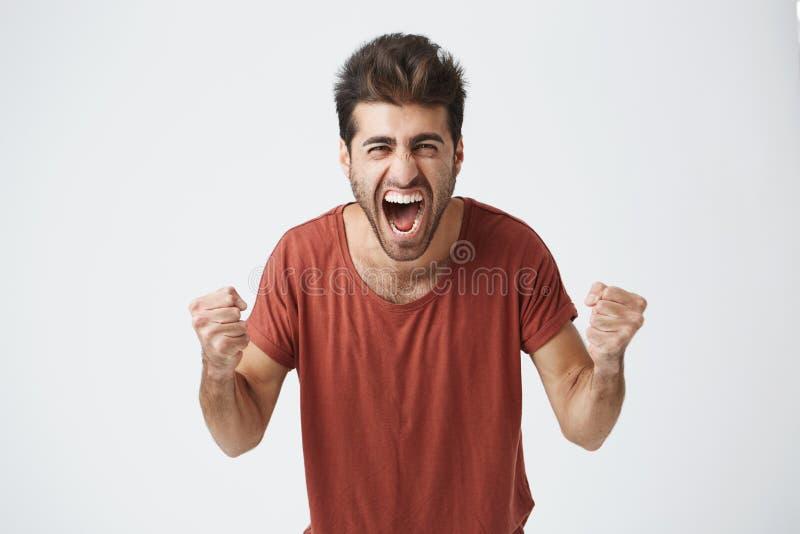 Glückliche positive aufgeregte zusammenpressende Fäuste des jungen Mannes und Schreien, tragendes zufälliges T-Shirt froh, gute N stockfotografie
