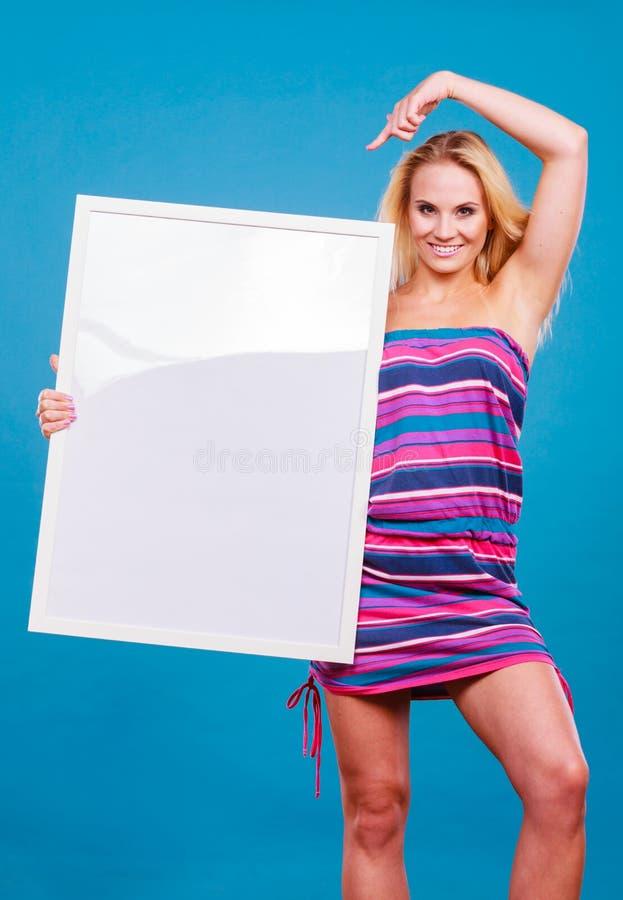 Glückliche positive Blondine, die leeres weißes Brett halten stockfotos