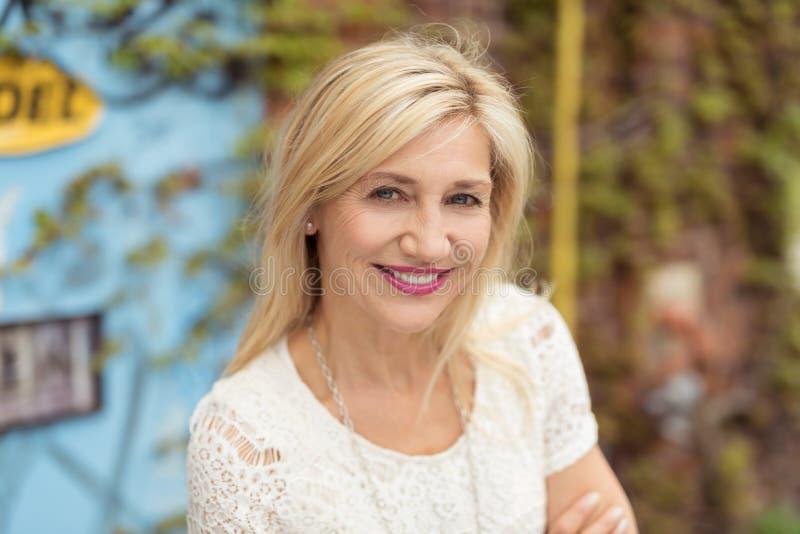 Glückliche recht blonde erwachsene Frau, die Kamera betrachtet lizenzfreie stockfotos