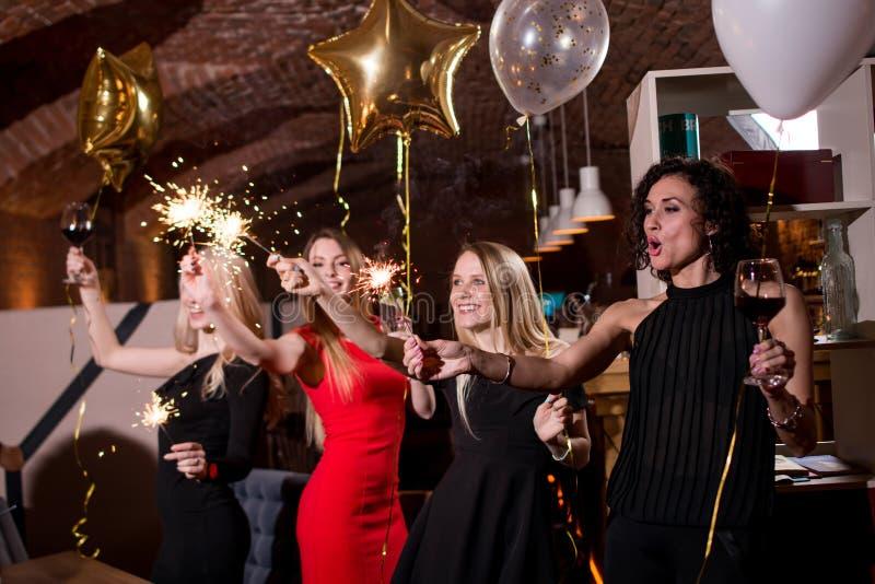 Glückliche recht junge Frauen, die Feuerwerkswunderkerzen, Ballone, Gläser Wein einen Feiertag im Restaurant mit feiernd halten stockbilder