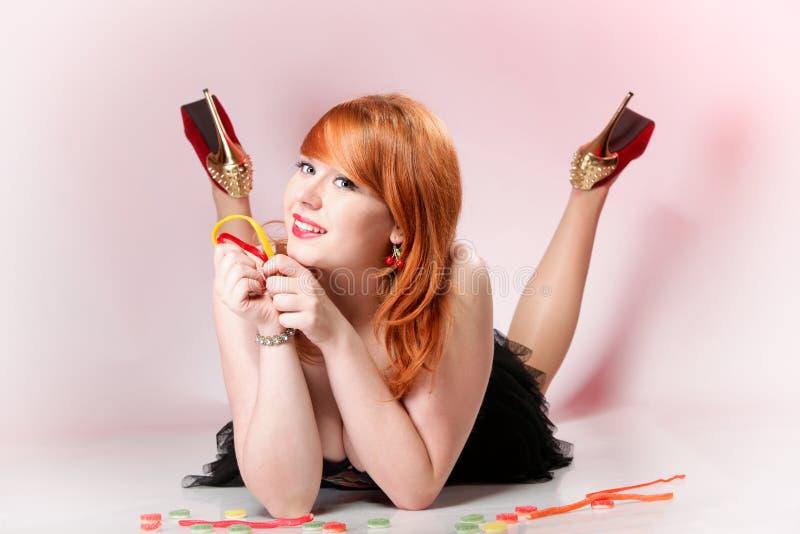 Glückliche redhair Frau mit gummiartiger Süßigkeit stockfotografie