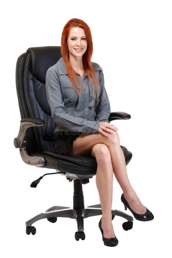 Glückliche Redheadfrau, die auf Stuhl sitzt stockfoto