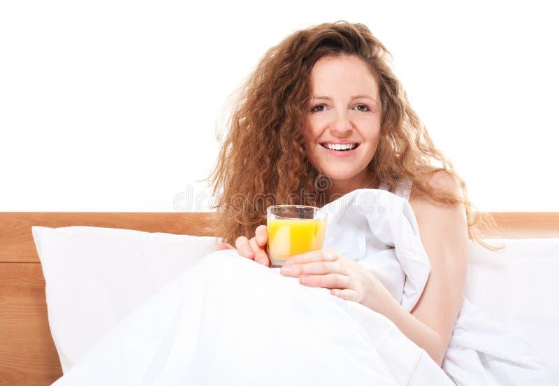 Glückliche Redheadfrau im Bett lizenzfreie stockfotos