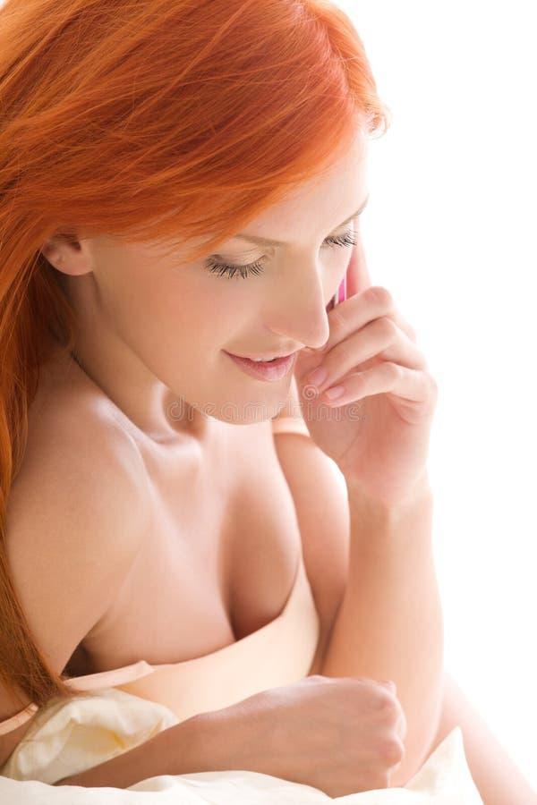 Glückliche Redheadfrau mit Handy lizenzfreie stockfotos