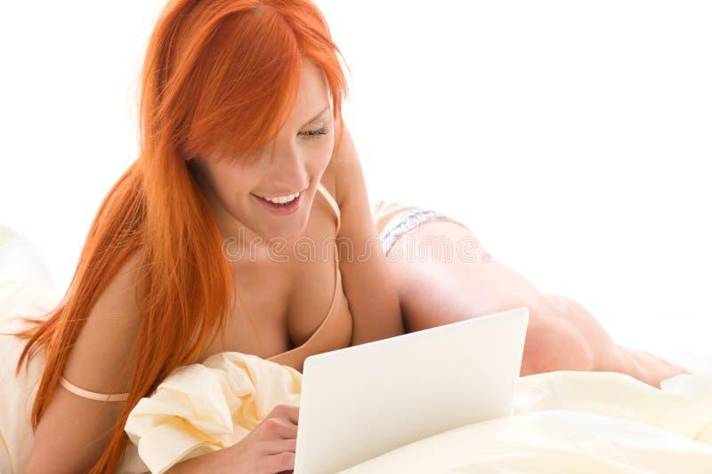 Glückliche Redheadfrau mit Laptop-Computer lizenzfreie stockbilder