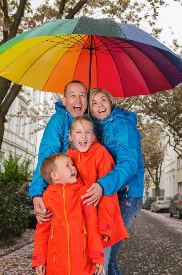 Glückliche Regenfamilie haben Spaß stockbilder