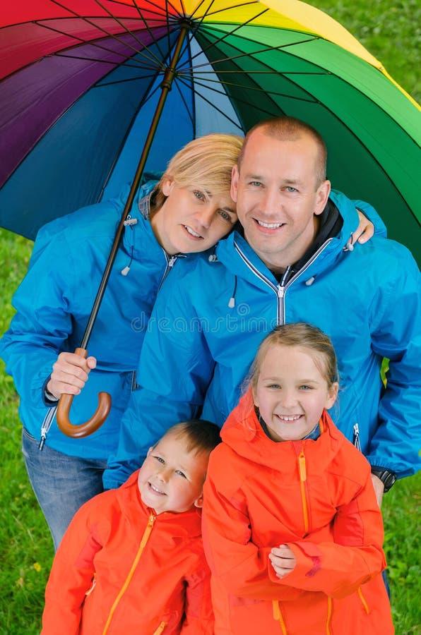 Glückliche Regenfamilie unter buntem Regenschirm stockfoto