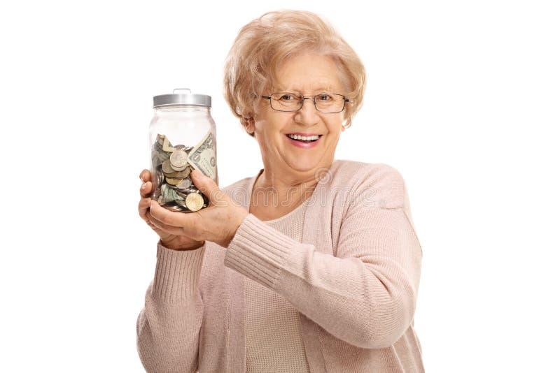 Glückliche reife Dame, die ein Glas hält, füllte mit Geld stockfoto
