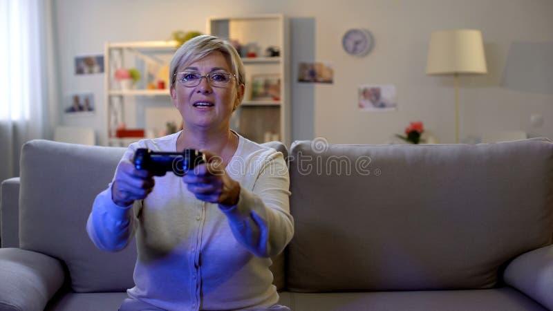 Glückliche reife Dame, die Videospiel auf der Konsole, nach Hause sitzend auf Sofa, Freizeit spielt lizenzfreie stockfotografie