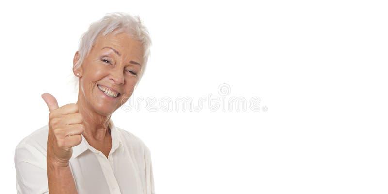 Glückliche reife Frau, die Daumen aufgibt lizenzfreies stockbild