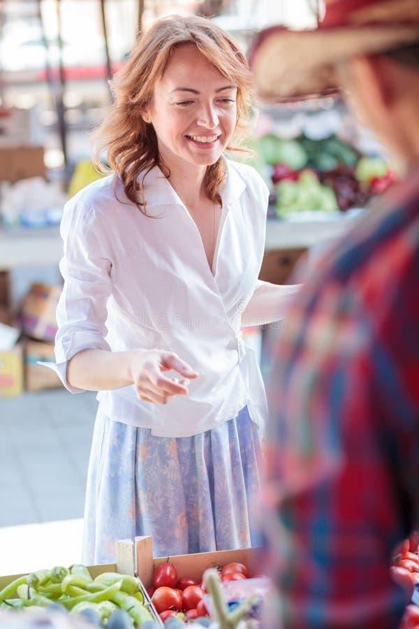 Glückliche reife Frau, die frisches organisches Gemüse in einem lokalen Markt kauft stockfotografie