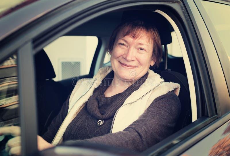 Glückliche reife Frau, die im Neuwagen sitzt lizenzfreies stockfoto
