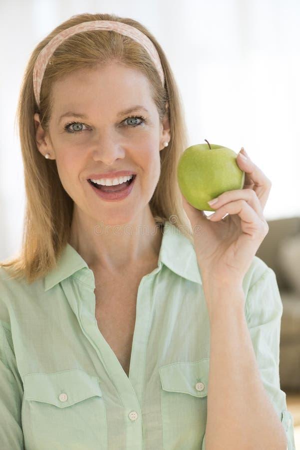 Glückliche reife Frau, die Oma Smith Apple At Home hält lizenzfreie stockfotografie