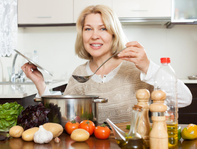 Glückliche reife Frau, die Suppe kocht stockbilder
