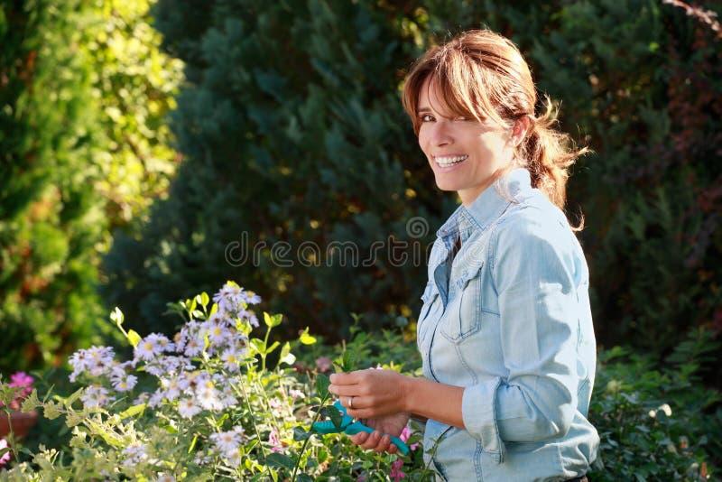 Glückliche reife Frau, die um ihren Blumen sich kümmert lizenzfreie stockbilder