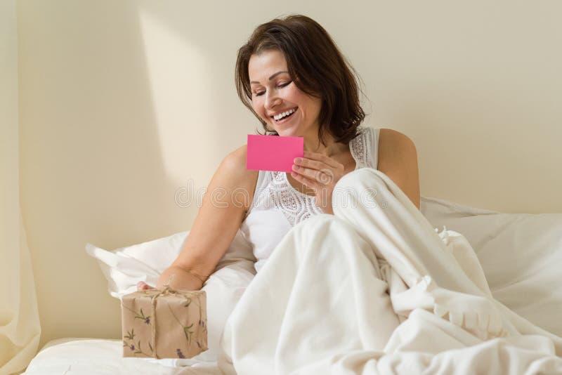 Glückliche reife Frau liest Grußkarte und betrachtet ein Überraschungsgeschenk und morgens sitzt im Bett stockbild