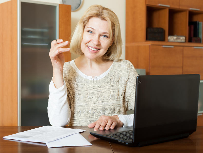 Glückliche reife Frau mit Laptop lizenzfreie stockbilder