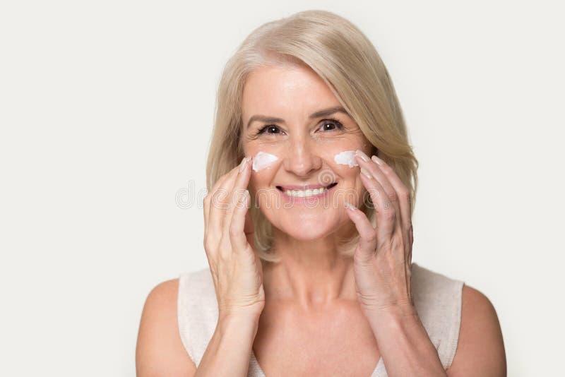 Glückliche reife Frau, welche die Kamera aufträgt Antialterncreme betrachtet stockfotos